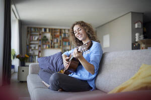 Smiling woman playing guitar while sitting on sofa at home - RBF07954