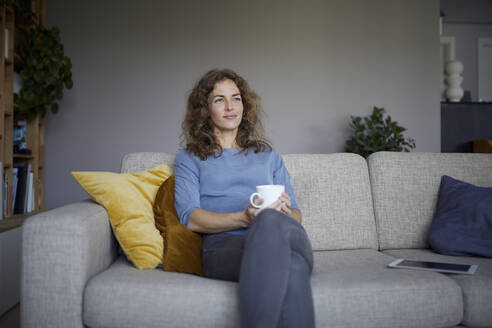Smiling with coffee cup woman looking away while sitting on sofa at home - RBF07975