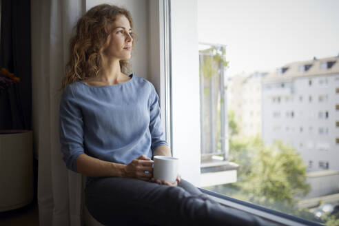 Woman with coffee cup looking through window while sitting on window sill at home - RBF07984