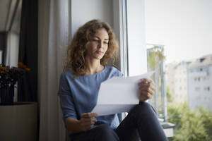 Woman reading paper while sitting on window sill at home - RBF07987
