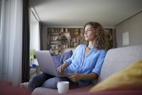 Woman using laptop while sitting on sofa at home - RBF07996
