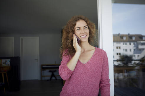 Woman talking on mobile phone while standing by door at home - RBF08014