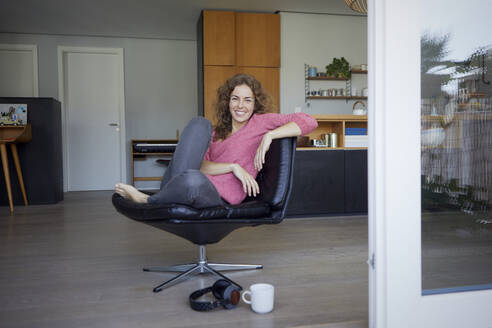 Smiling woman sitting on chair at home - RBF08020