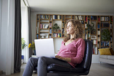 Mid adult woman using laptop while sitting on chair at home - RBF08023
