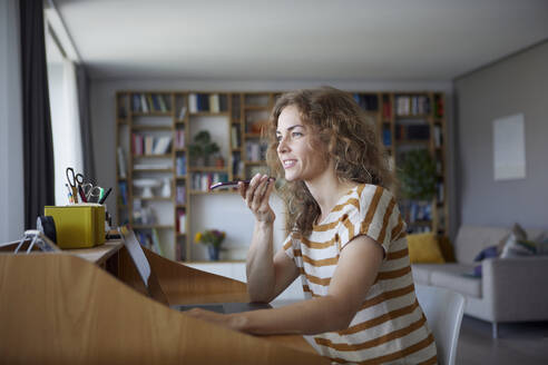 Woman talking on mobile phone while sitting by desk at home - RBF08029
