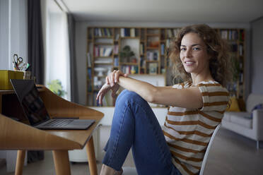 Woman smiling while sitting by desk on chair at home - RBF08032