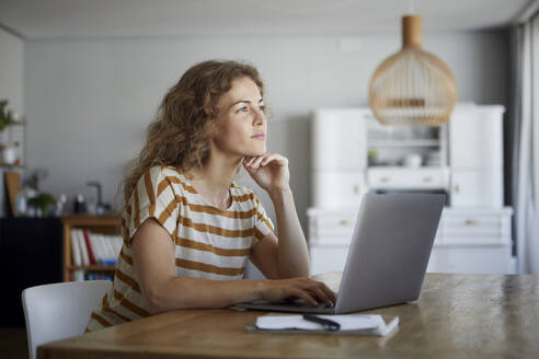 Thoughtful woman with head in hands using laptop while sitting by table at home - RBF08035