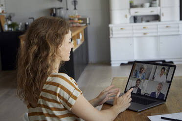 Woman talking on video conference through laptop while sitting at home - RBF08038
