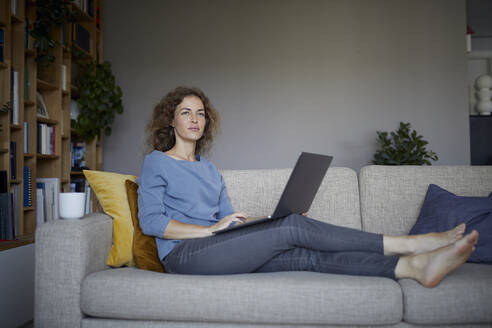 Woman looking away while using laptop sitting on sofa at home - RBF08044