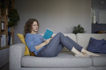 Woman reading book while sitting on sofa at home - RBF08047