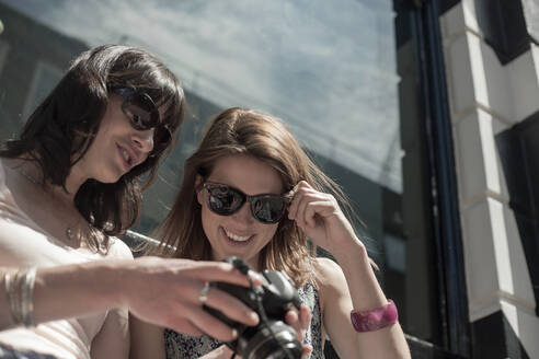 Smiling woman looking at camera held by female friend in city on sunny day - AJOF00178