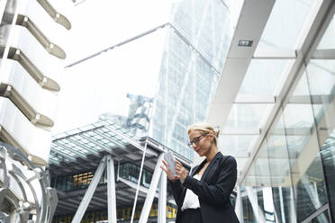 Beautiful female professional using smart phone while standing against office building at downtown district - PMF01292