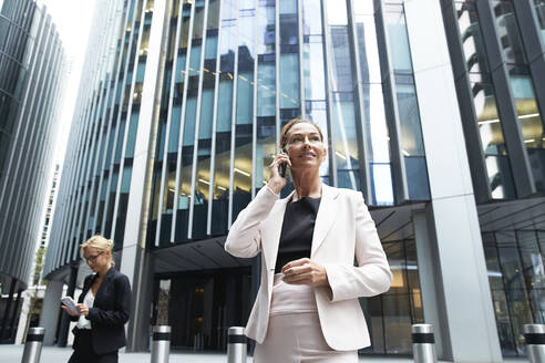 Female professional talking on mobile phone while standing near businesswoman against modern office building - PMF01298