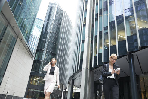Female professionals walking with mobile phones against office building at downtown district in city - PMF01301