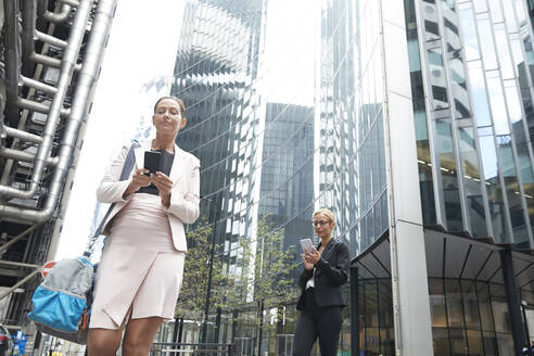Mature businesswomen using smart phones against modern office building at downtown district - PMF01304