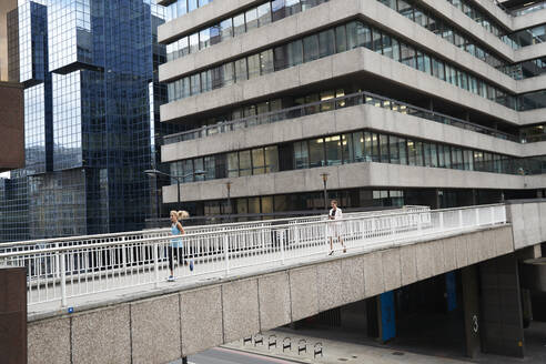 Female entrepreneur using mobile phone while woman jogging on footbridge against office building in city - PMF01310