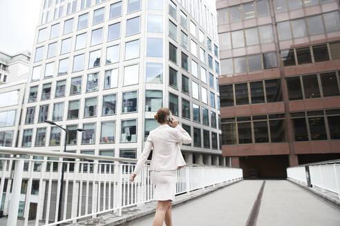 Female entrepreneur talking through mobile phone while walking on footbridge at downtown district - PMF01313