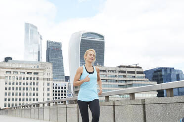 Mature blond woman running on footbridge against modern office buildings at downtown in city - PMF01322