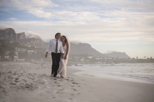 Happy newly married couple walking at beach against sky during sunset - AJOF00187