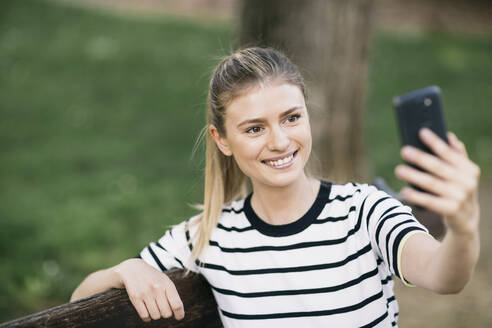Beautiful woman taking selfie on smart phone while sitting in public park - ABZF03419