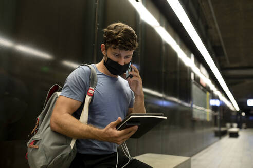 Young man wearing protective face mask talking on phone while holding digital tablet at subway during pandemic - VABF03587