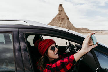 Spain, Navarre, Female tourist leaning out of car window taking smart phone photos of Bardenas Reales - EBBF00852
