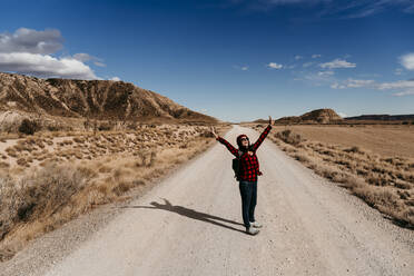 Spain, Navarre, Female tourist standing with raised arms in middle of empty dirt road in Bardenas Reales - EBBF00861