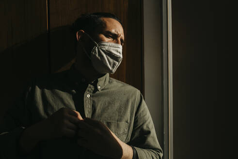 Man wearing protective face mask while looking away at home - DSIF00177