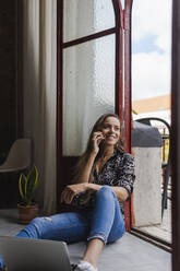 Smiling creative businesswoman talking on mobile phone while sitting at doorway in office - DCRF00939