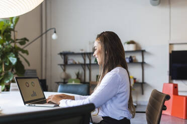 Smiling businesswoman using latptop while working at desk in office - DCRF00942