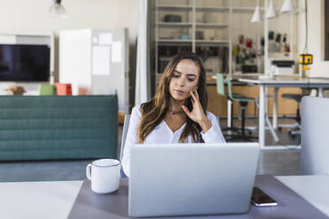 Businesswoman thinking while looking at laptop in office - DCRF00948