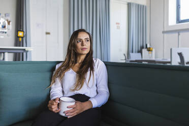 Thoughtful businesswoman with coffee mug on sofa in office - DCRF00951