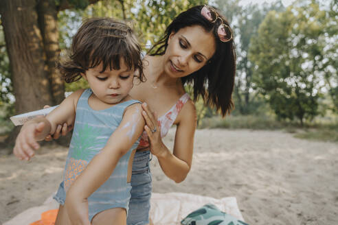 Mother applying sunscreen to daughter at beach - MFF06245