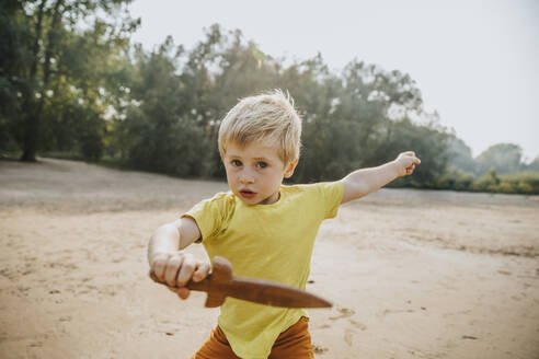Cute little boy playing with wooden dagger at beach - MFF06251