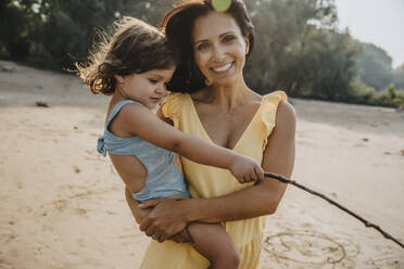 Smiling mother holding daughter in arms while standing at beach - MFF06281