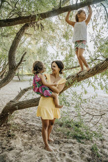 Mother and daughters standing near willow tree - MFF06299