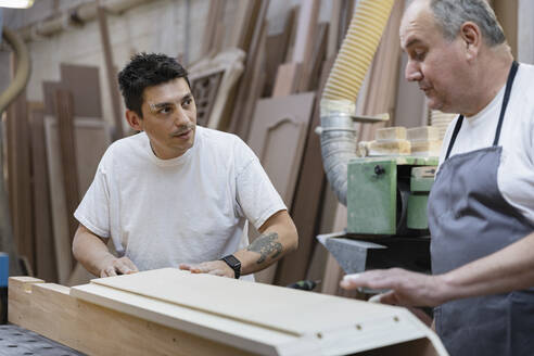 Artist discussing while standing by workbench at workshop - EIF00258