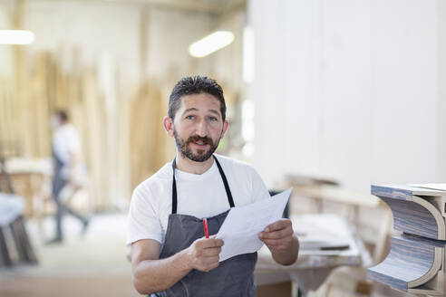 Smiling man holding paper while standing at workshop - EIF00267