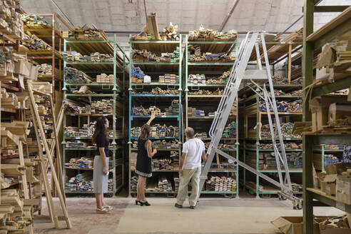 Employee and coworker choosing ornate wood panel while standing at warehouse in factory - EIF00288