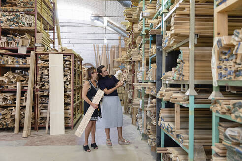 Women choosing ornate wood panel while standing in warehouse at factory - EIF00291