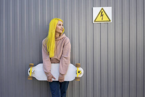 Young woman looking away while holding skateboard standing against metal wall - VPIF03127