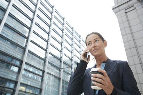 Smiling businesswoman drinking coffee while talking on mobile phone in city - PMF01328