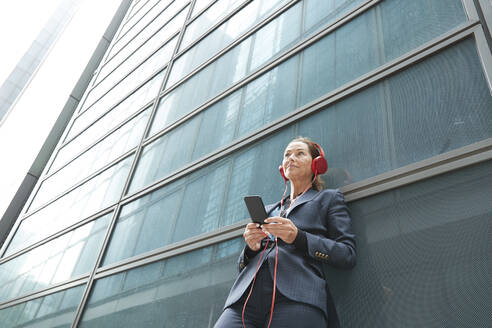 Businesswoman with headphones listening music while standing against building in city - PMF01340