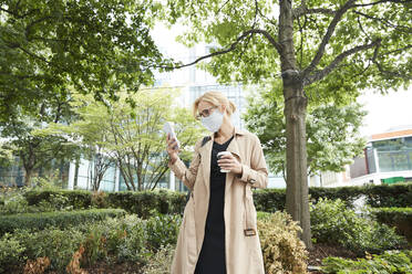 Businesswoman holding coffee cup while using mobile phone in city - PMF01346