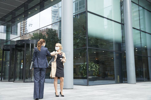 Business people wearing face mask greeting with elbow bump against office building - PMF01364
