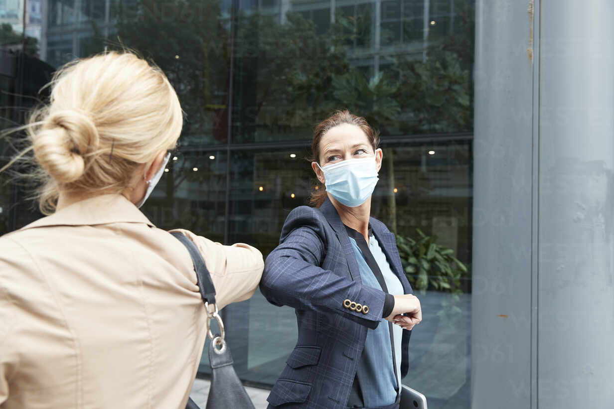 Businesswoman and colleague with face mask greeting with elbow bump while standing against office building - PMF01370 - Pete Muller/Westend61