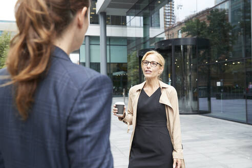 Colleague talking with businesswoman standing st distance in city - PMF01373