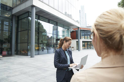 Colleague looking at businesswoman using laptop while standing against office building - PMF01376