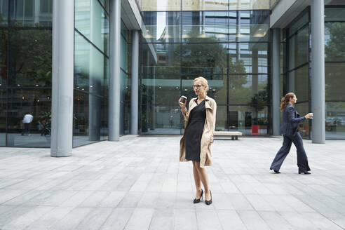 Woman drinking coffee with businesswoman walking in background at city - PMF01379