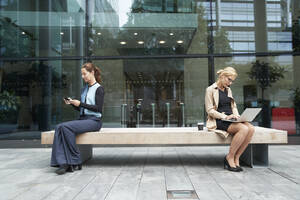 Businesswoman and colleague working while sitting with social distance on bench against office building exterior - PMF01385